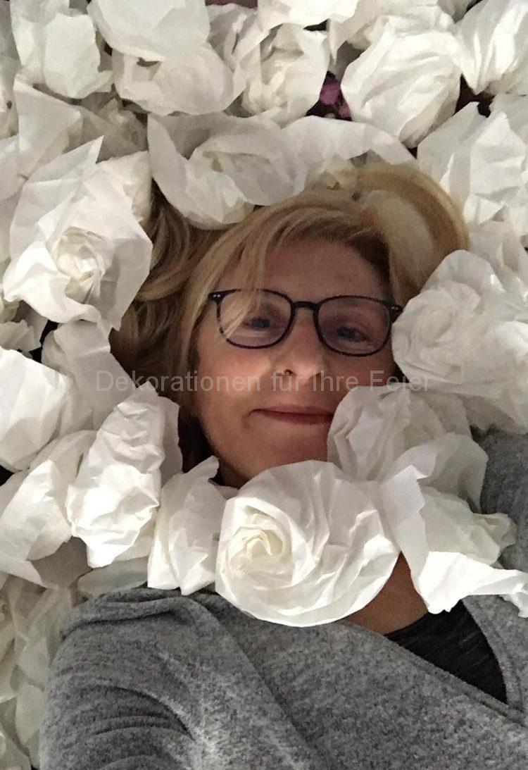 Aus Butterbrottütten gefaltete weiße Rosen .