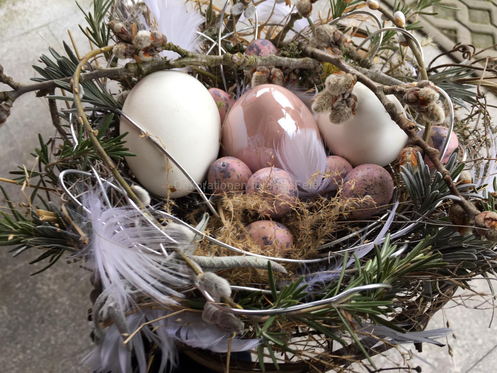 Nest aus Holzzweigen und für Ostern mit Eiern osterfestlich dekoriert