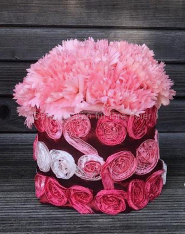 Rosa Nelken dicht einander in einer Vase  umhüllt mit farbig passenden dreifarbigen Stoff .
