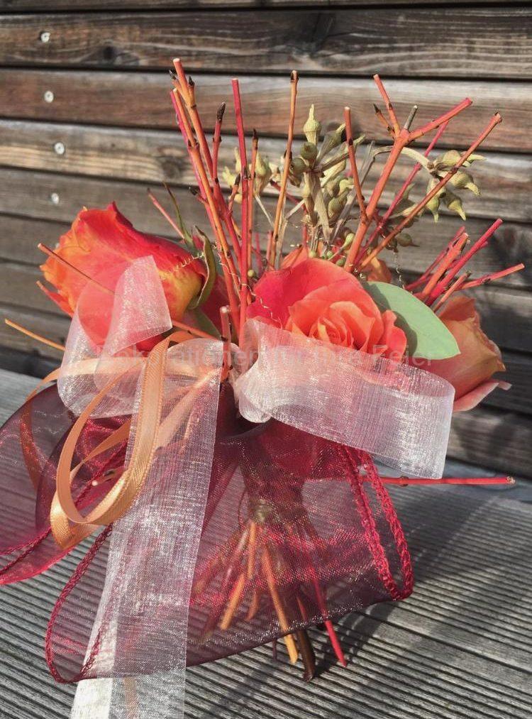 Stehe Sträußchen .Orange gelbliche dicke Rosen stehen in gleichfarbigen Ästchen  zusammen gebunden von gleichfarbige Organza Bänder