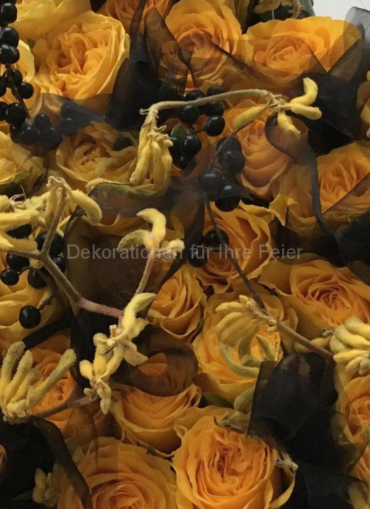 Ein Detail aus Trauer Gesteck -gelbe Risen umhüllt mit schwarzen Tüll .Zwischen den dicht gesteckten Rosen  sieht man schwarze Liguster Beeren und kleine Knospen .