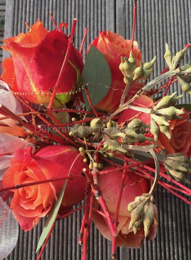 Aus der Vogelperspektive das Sträußchen aus orange-gelben Rosen und gleichförmigen Ästchen .