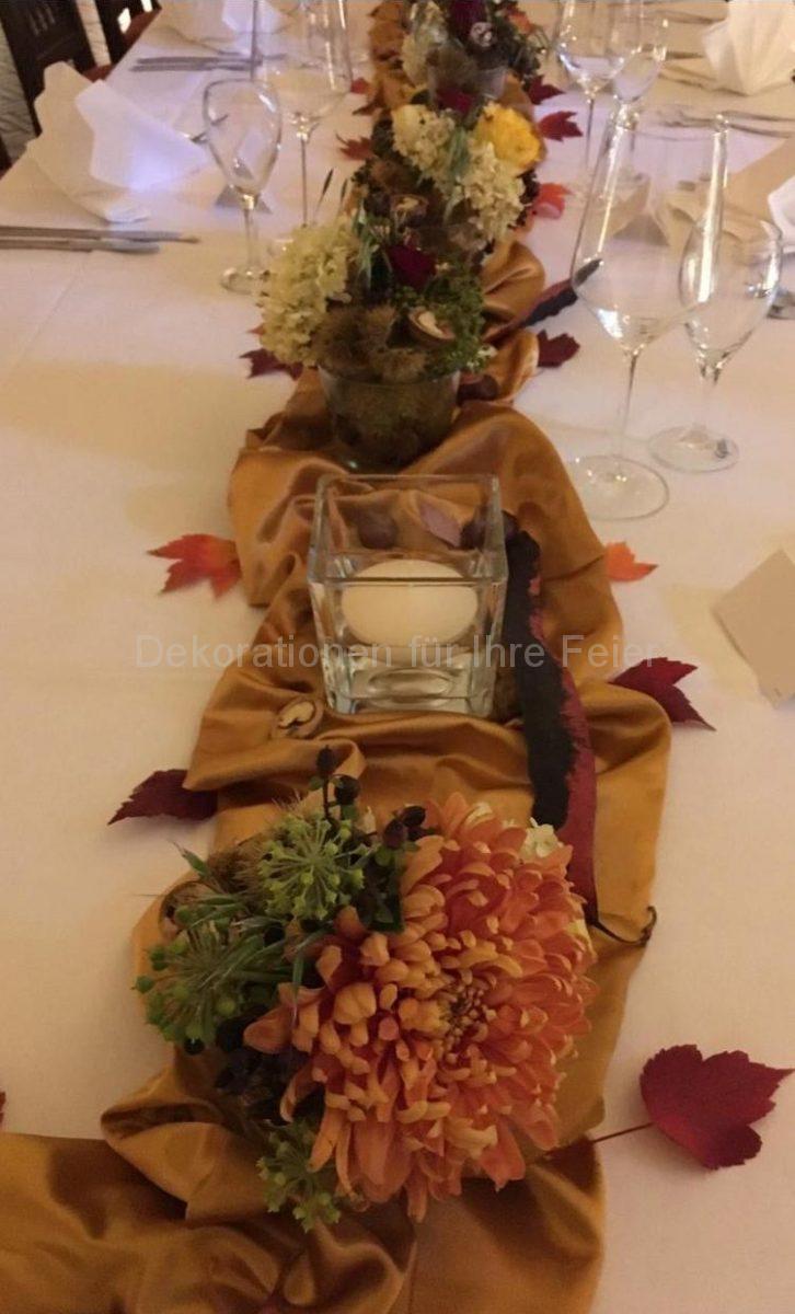Herbstlich geschmückter Tisch in warmen Herbst Farben .Chrysanthemen in einer Kombination mit herbstlichen Beeren und Früchten .Wallnpss Hälften ,Esskastanie Gehäuse .Abwechselnd auf dem seidigen Tischläufer sind Schwimmkerzen in Glas mit wasser gestellt .Links und rechts liegt klein Laub in bunten Herbst Farben