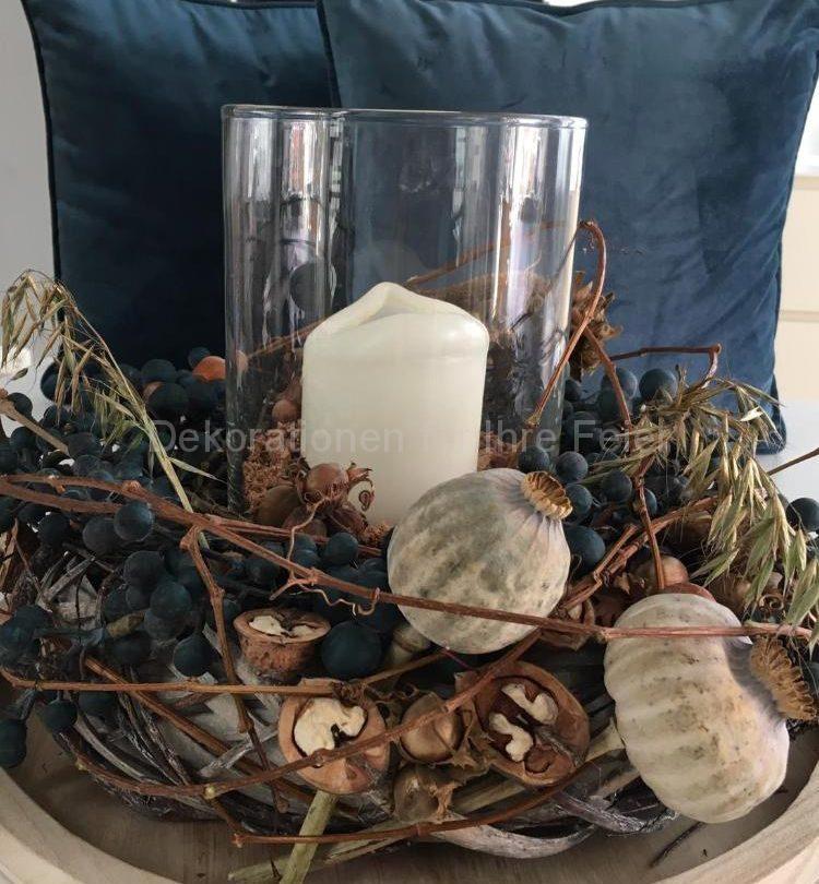 Eine in Natur Tönen und Petrol blau Kombination .Windlicht Glas mit dicke Kerze mitten in einem trockenen Kranz ,geschmückt mit trockenen Mohn Kapseln ,Wallnuss Hälften und unechten petrolfarbenden  dicken Beeren .Dazu passende Samt Kissen in gleichen Ton .