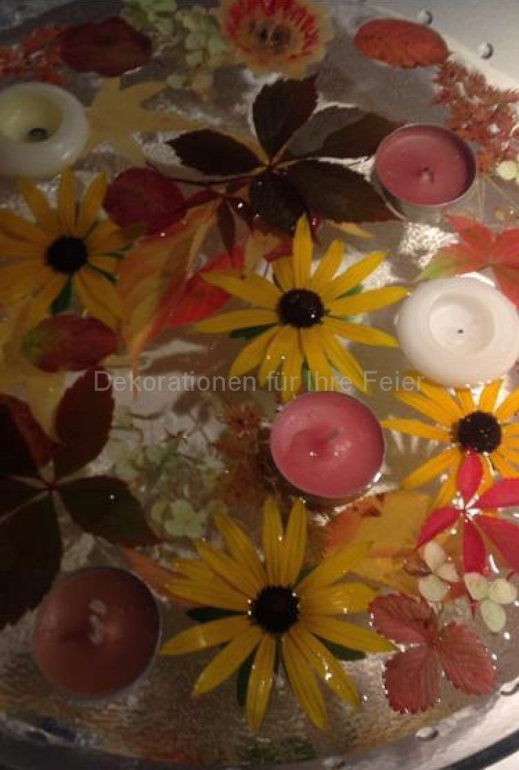 Herbstliche Dekoration .Flache breite Glas Schalle gefüllt mit Wasser .Drauf schwimmen bunte kleine Blätter ,kleine Blüten und Schwimm- Kerzen .Eine Augenweide .