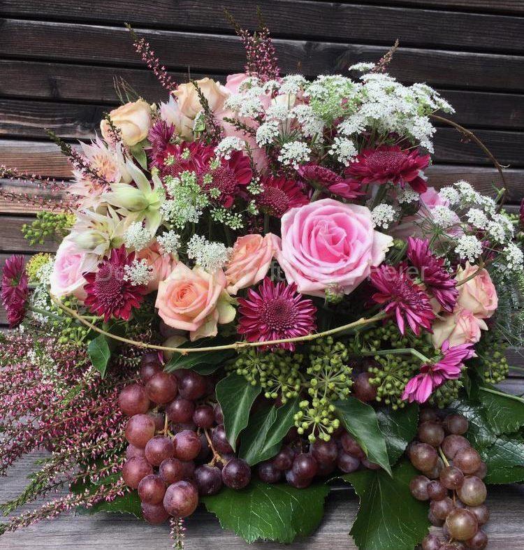 Ein herbstlicher Gesteck kombiniert aus Blumen und Obst.Von rosa bis dunkelrot, dunkel pink Chrysanthemen mit rosa Rosen ,und Erika Pflanze ,Efeu Beeren und dunkel rote Trauben schmücken den Gesteck .Angelockter ist alles mit Wiesen Blumen