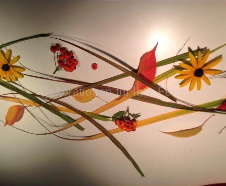 Herbstliche Stimmung auf dem Tisch .Als Tischläufer gestellt sind breitere herbstliche Gräser Halme,begleitet in unregelmäßigen Abständen mit bunten Laub ,Beeren und kleinen Blüten .