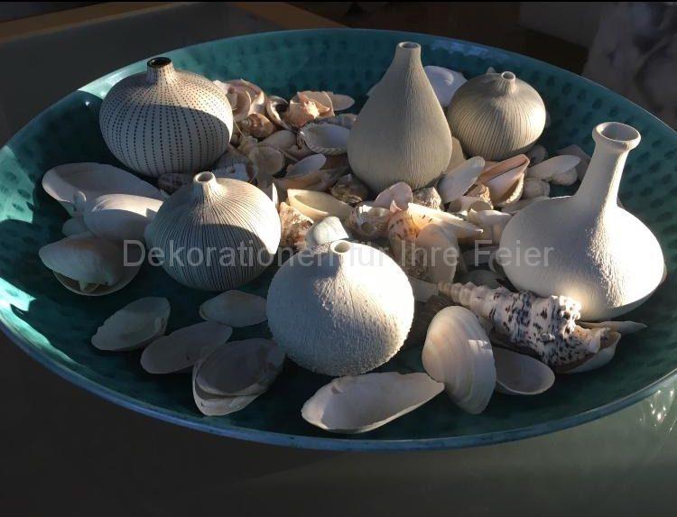 Ein Stillleben mit Maritime Note .Ein Türkis Teller mit ganz schlichten weißen kleinen Vasen ruht in eine Vielfalt von gesammelten Muscheln