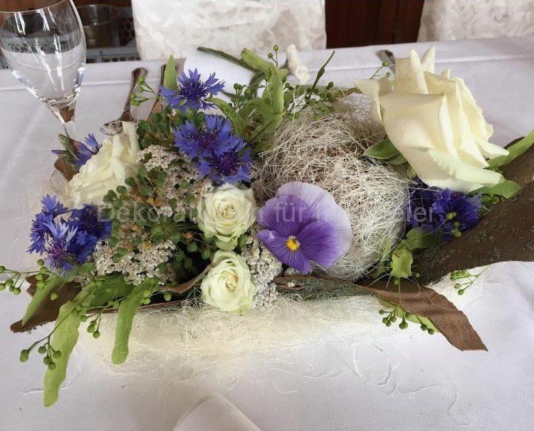 Hochzeitstisch Deko .Im blau weiß .Für naturverbundene .Eine dicke weiße Rose mit vielen kleinen Blüten -von Feld und Wiese : Kornblumen,Stiefmüterchen mit kräftigen blau -lila Ton und zum auflockern-Lindenblüten .Blumen Gesteck ist umhüllt in Baumrinde und Natur Bastwolle was gibt noch natürlichen Charakter .