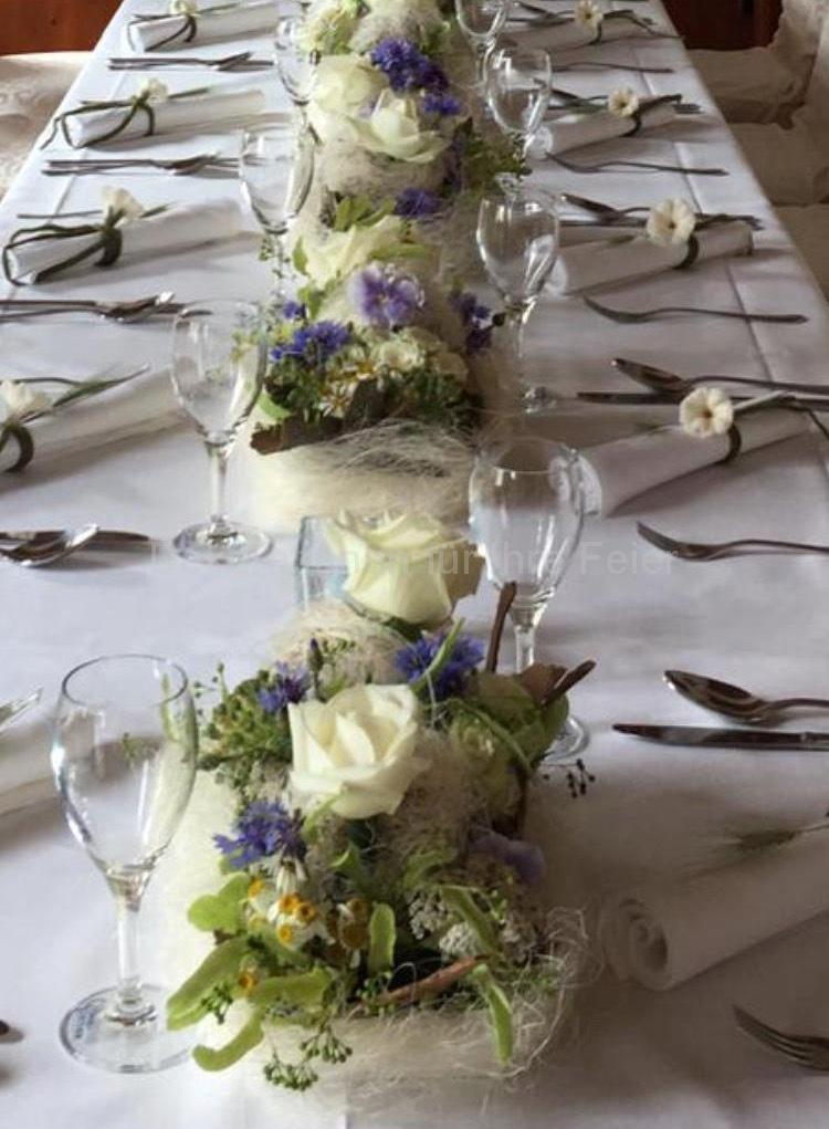 Blauweiße Hochzeitstisch-Deko, weiße Edelrosen in Gesellschaft von zarten Stiefmütterchen, Feldblumen, Lindenblüten und Wiesenblumen. Sorgfältig abgestimmt ergibt dies eine besonders feierliche Note