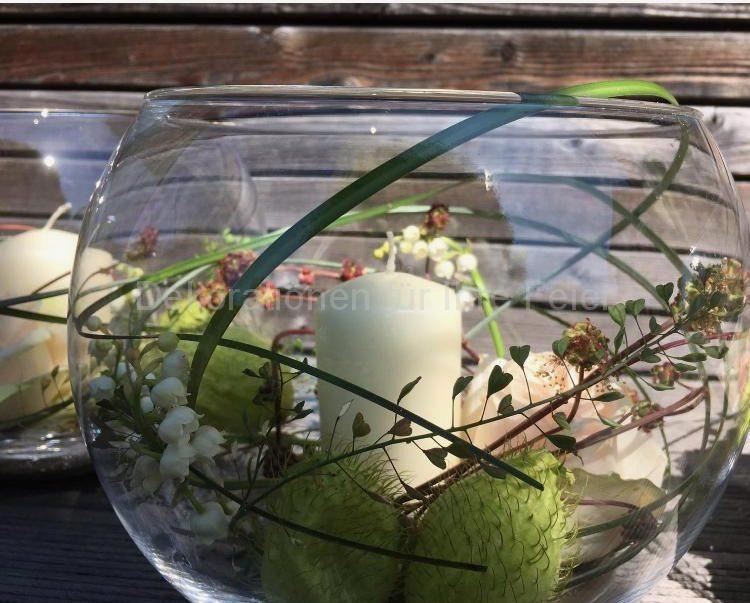 Aquarium Glas Vasemit eine Kerze und geschwungenen Wiesen Blüten.