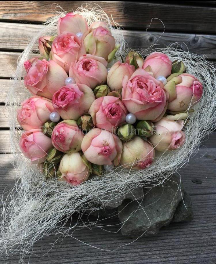Ein Brautstrauß in Herzform mit vielen kleinen geschlossenen rosa Rosen-Knospen. Hier und da schaut eine weiße Perle raus, das Herz ist in weißes Kokos-Haar gewickelt