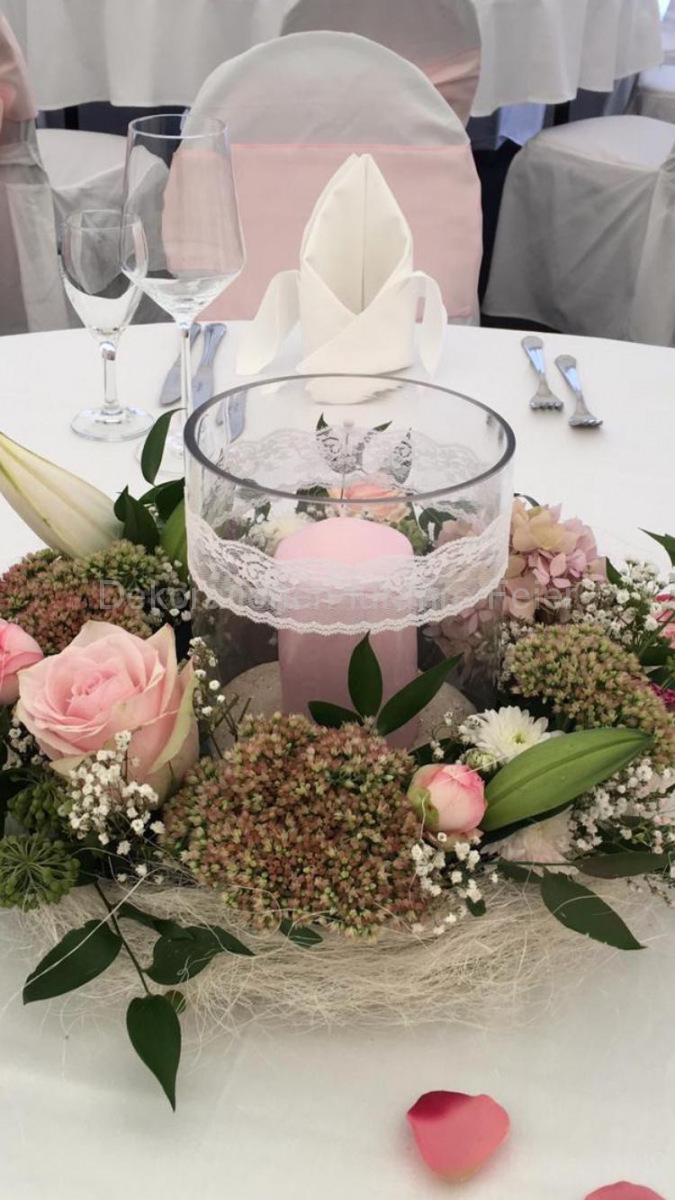 Hochzeitstisch rund, Rosa-weißer Blumenkranz aus verschiedenen großen und kleinen Blüten. Mittig befindet sich ein passender Zylinder als Windlicht-Vase mit großer zart-rosa Kerze. Das Glas ist umrundet mit weißer Spitze, einzelne Rosen und rosa Blütenblätter ruhen auf dem Tisch. Ein Traum für jede Prinzessin!