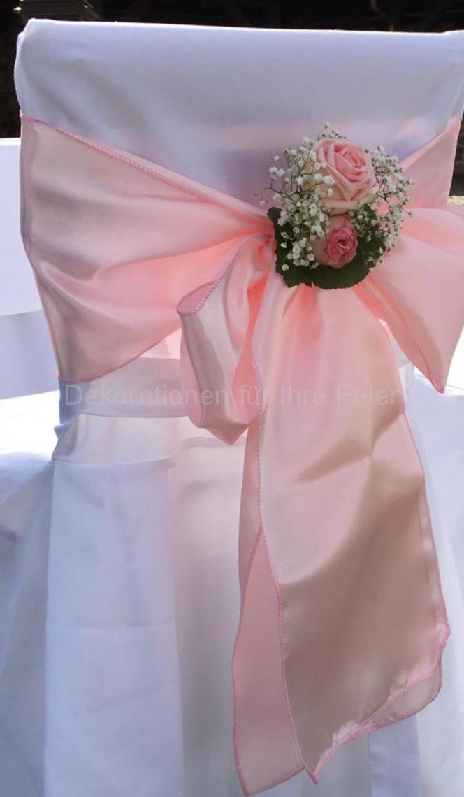 Ein Beispiel für den Schmuck der Stühle für das Brautpaar. Bei der Frei-Trauung oder auch im Raum. Weißer Stoff über die Stühle überzogen macht einen feierlichen Eindruck. Breite Satin-Bänder hinten fest gebunden halten kleine Rosen-Sträußchen fest. Der Schmuck ist dem Brautstrauß farbig und förmlich angepasst.