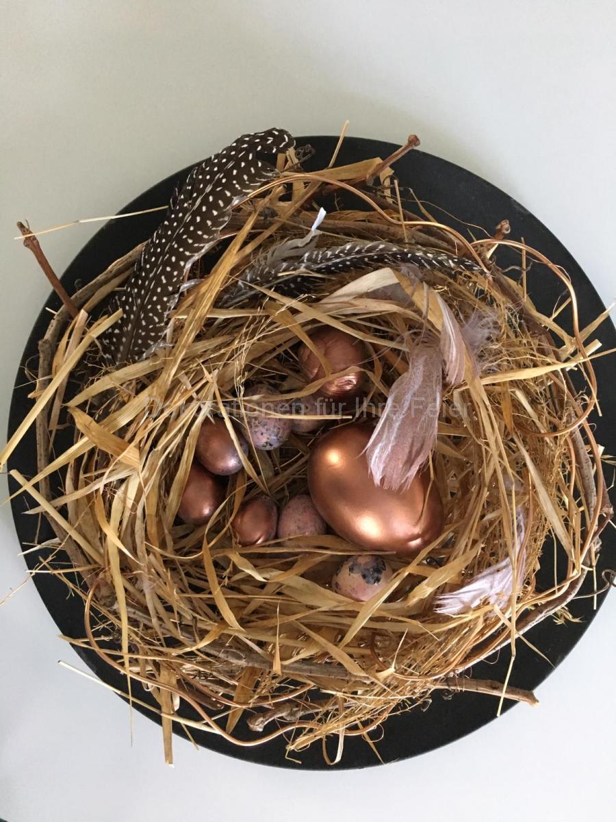Osterteller aus Vogelperspektive.Auf den schwarzen Teller ist ein strohgebundener  Nest mit bronzegefärbten Hühner Eier und Wachteleier.Schwarz-weiß gepunkte Feder mit leicht Bronze gefärbten Feder