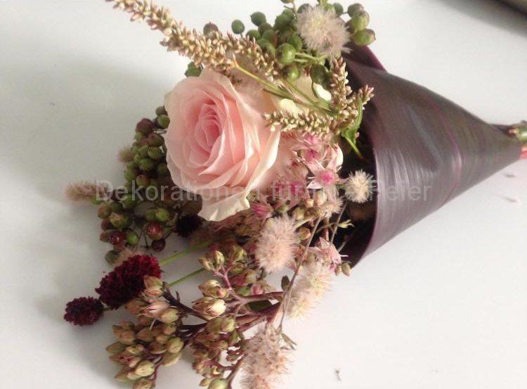 Warum nicht mal eine Schultüte für das Brautpaar? Es beginnt ja auch die Schule des gemeinsamen Lebens! Hier ist sie gefertigt Ton in Ton aus einem großem gerollten Blatt mit kleinen Blüten und Gräsern. In der Rose finden die Ringe ihren Platz bis zum Ja-Wort.