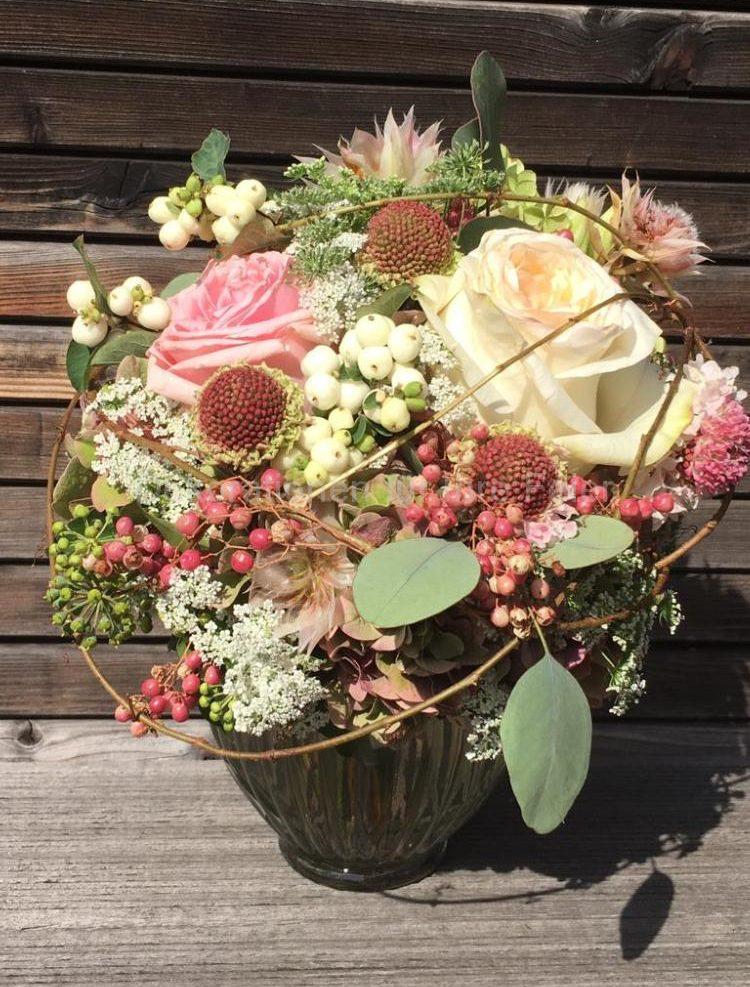 Ein prächtiger Brautstrauß in Pastellfarben, von weiß über Natur-weiß, über Lachsfarbe in mehrere rosa Töne übergehend. Bewegung in den Strauß bringen verschiedene Beeren, Ranken und Eukalyptus-Blätter