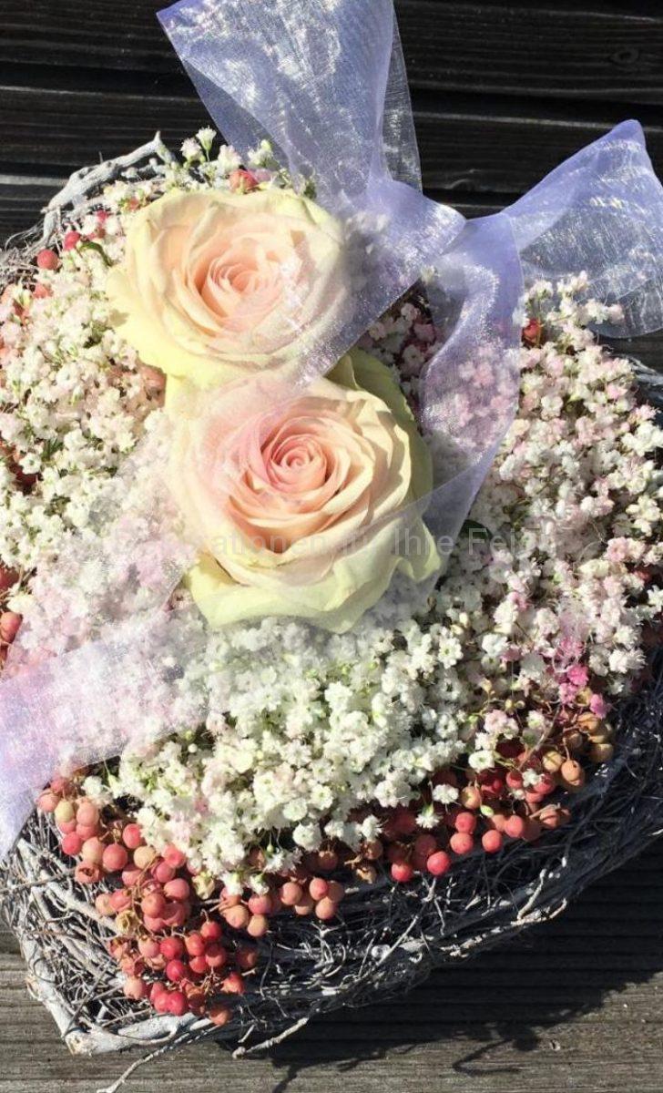 Ringhalter im Herzform von Herz zu Herz! Wunderschöne rosa Rosen liegen auf weichem weißen Schleierkraut-Bett, das ganze ist umrundet mit trockenen rosa Pfeffer, einer weißen Tüll-Schleife. Dazu wird das Herz auf den Händen zum Standesamt oder in die Kirche getragen. In den beiden Rosen finden die Ringe ihr Platz