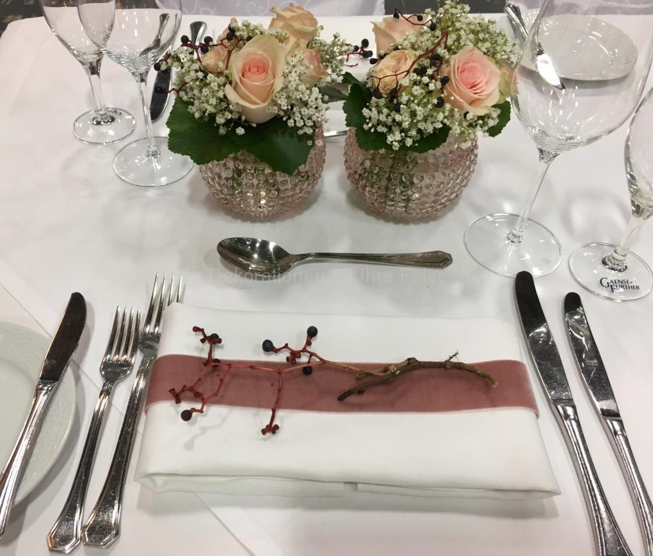 """Für die schmalen Tische auch ein Traum im rosa-weiß. Runde rosa Vasen gefüllt mit rosa Rosen und weißem Schleierkraut. Runde """"Galax-Blätter"""" runden das ganze perfekt ab. Servietten-Schmuck ist mit passenden Satin Band beschickt, darauf ruht ein Zweig von wilden Beeren, harmonisch passend zum Ganzen!"""