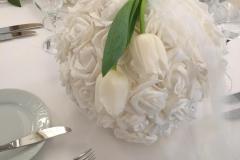 weißer Rosenstrauß in Vase auf dem gedeckten Hochzeitstisch