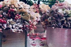 Zwei mal trocken Hortensien Gesteck mit rosa Pfeffer .Einmal in viereckigen Holz Kästchen ,einmal in runden rosa Töpfchen .Beides steht auf einen weißen spitzenförmigen Metall Tablet .