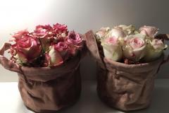Zwei samtflauschige  Körbchen halten frische Rosen -rosa Töne ,Kopf an Kopf in frischsteckmassen Block .