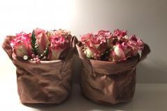 Zwei identische schöne Blumenvasen aus Stoff in Kupfer-Farben mit rosa bis rot farbige Sträuße