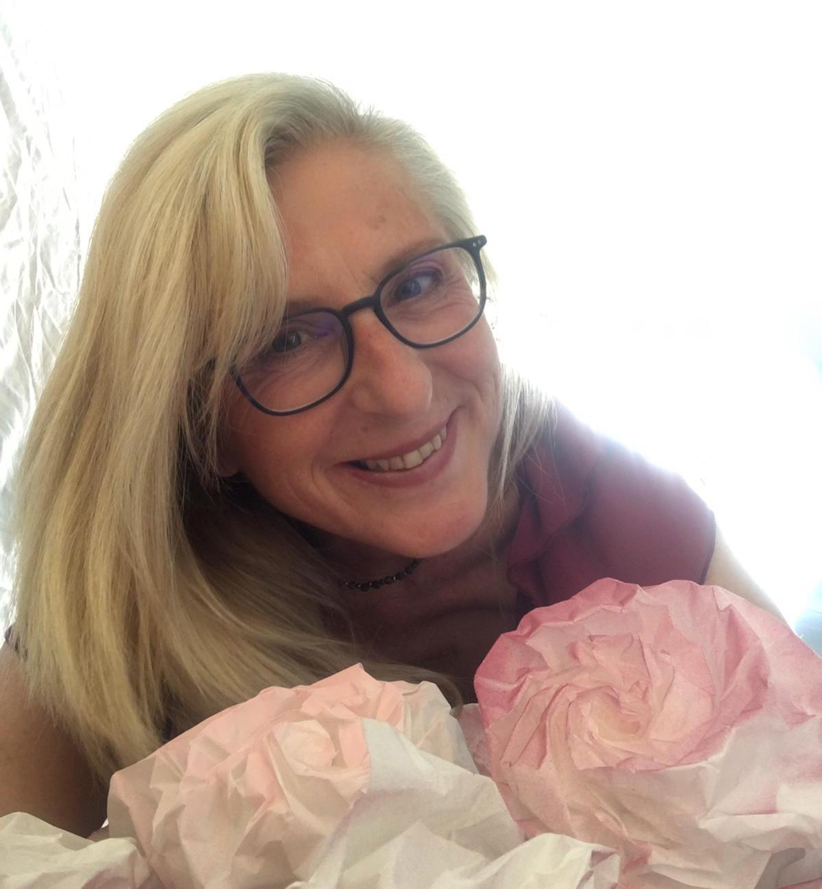 Bild von Lidija Schlieker mit rosa und weißen Blumen vor sich