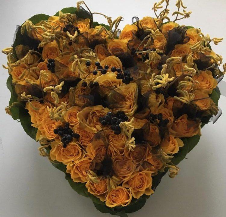 Ein Trauer Herz aus gelben Rosen ,schwarzen Beeren und schwarzen Tüll .