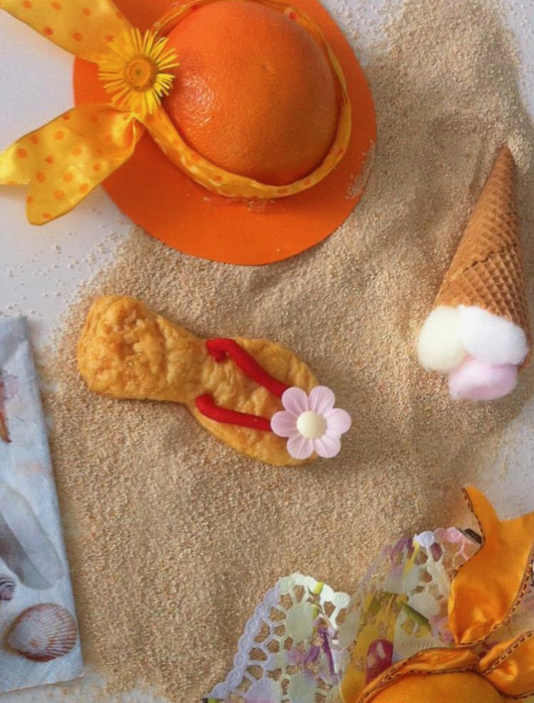 Sommer Erinnerungen : Sommerhüte aus halbierten Orangen und halbierten Pampelmuse,geschmückt mit Stoffbänder und bunten Papier als Hut Krempe . Eiswaffeln mit farbigen Watte Puscheln, Flips -Flops aus Blätterteig gebacken und essbaren Bänder und Zucker Blüten geschmückt . Alles liegt auf eine sandige Landschaft aus Semmelbrösel .