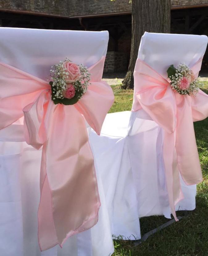 dekorierte Sessel für das Brautpaar, mit rosa Schleifen auf weißem Stoff
