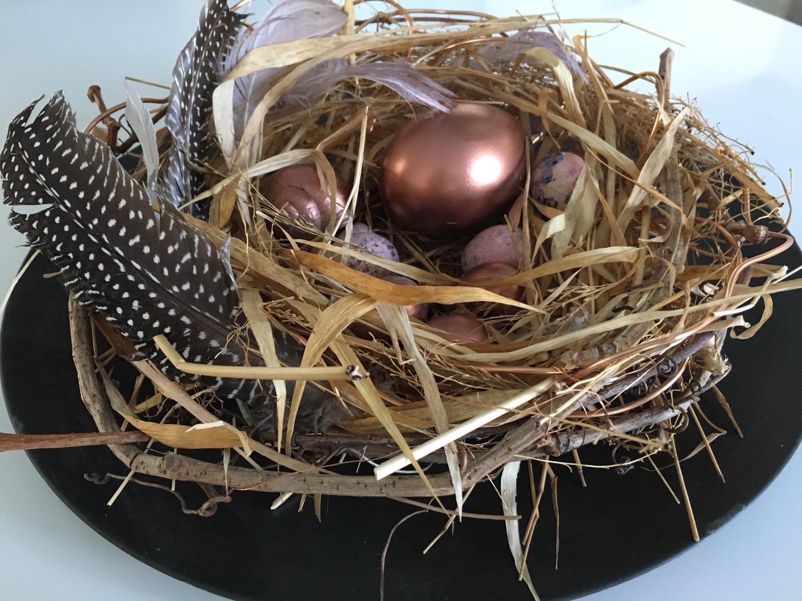 Ostern Nest aus Stroh geflochten.geschmückt mit Perlhühn Feder ,auf schwarzen Teller .In der Mitte sind einige bronzegefärbte Eier in verschiedenen Größen