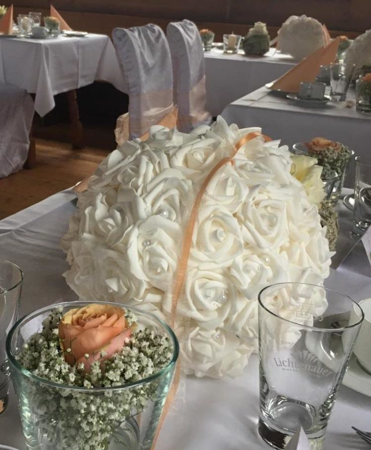 Hochzeitstisch-Deko, weiß mit aprikot-farbigen Akzenten. Der Tisch wird geschmückt mit weißen Rosenkugeln zur beiden Seiten fließend auf dem Tisch drapiert, aprikot-farbene Bänder, kleine Vasen mit passender aprikot Rose mit weißem Schleierkraut. Dazu passendes Islandmoos-Kugel mit weißer Rose wiederholt sich im gleichen Rhythmus auf dem Tisch. Kleinere Kerzen im Windlicht-Glas geben bezaubernde Lichteffekte