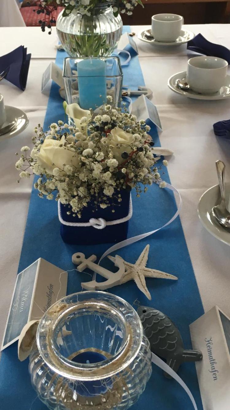 blauer Tischläufer mit kleine viereckigen Vasen gewickelt in blaues Vlies mit einem Seemansknoten  Kordel gebunden.  Mehrere Meeres Symbole wie Anker und Muscheln schmücken den Tisch.  Kleine hell blaue Kerzen befinden sich abwechselnd mit kleinen passenden weißen Sträußchen auf dem Tisch